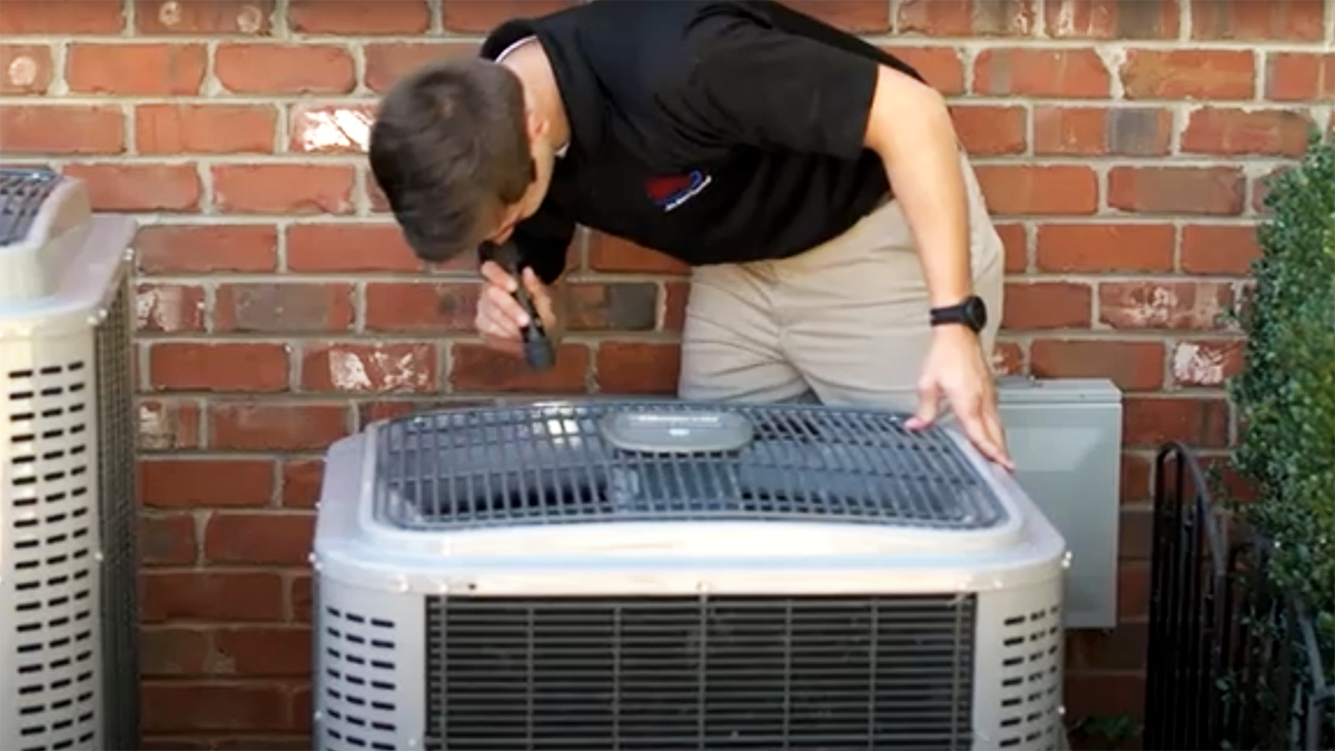 Jake, one of our home inspectors, looking at an air condition unit outside of a house