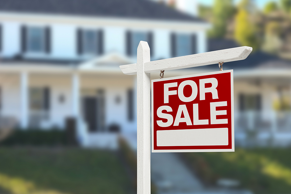For sale sign in front of a house after thorough home inspection services were provided